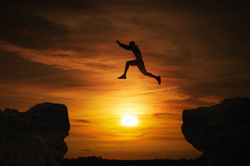 Fototapeta Silhouette of a man jumping over abyss at sunset with copy space