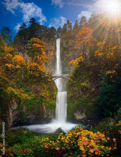 Multnomah Falls in Autumn foliage colors with shining sun