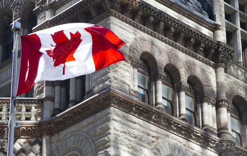 Spoed Foto op Canvas Canada Beautiful Canada flag is waving front of a historical building