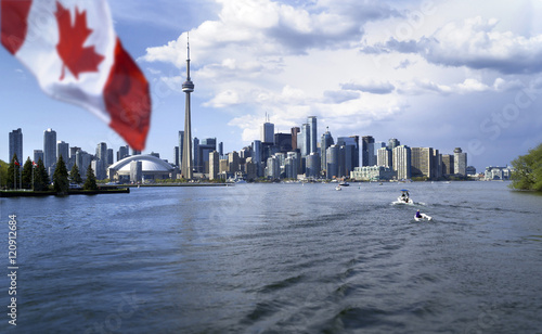 Deurstickers Toronto Beautiful Canada flag is waving front of famous Toronto City view