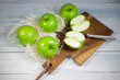 green apples and on wooden background, top view