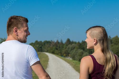 Fotografie, Obraz  Junges Paar schaut sich beim Spaziergang verliebt an