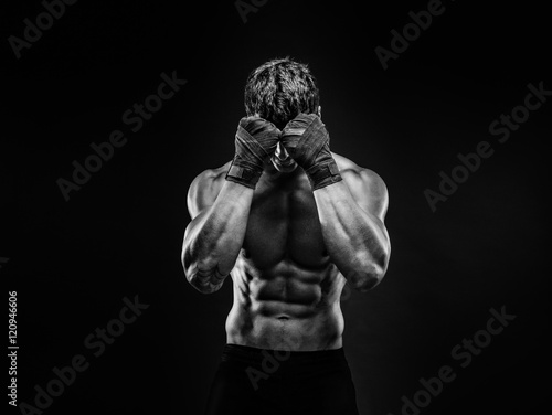 Valokuva Unrecognizable topless man in fighting gloves covering face with fists on black background