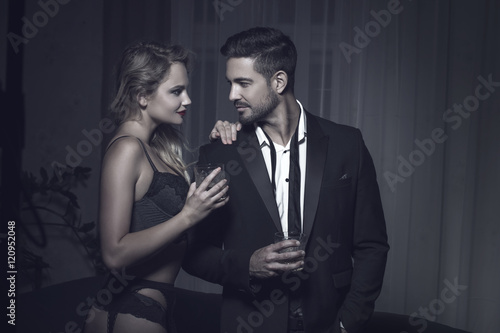 Fototapeta Rich macho young man drink whiskey with blonde lover obraz