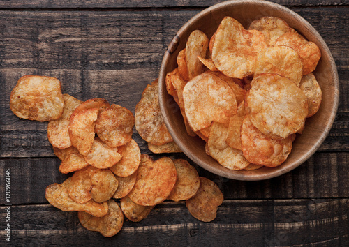 Cuadros en Lienzo Bowl with potato crisps chips on wooden board
