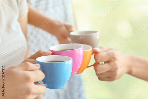 Fotografering  Group of people holding cups of coffee together