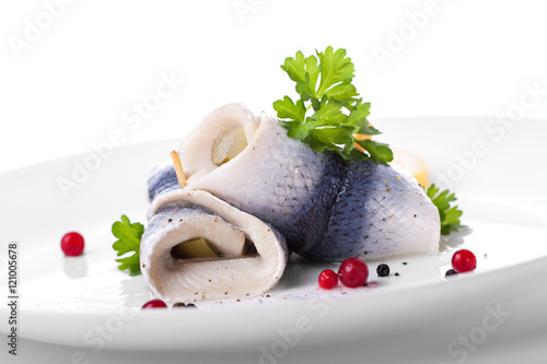 Fotografie, Obraz  Rollmops (rolled marinated herring) with marinated cucumber, salt, pepper and pa