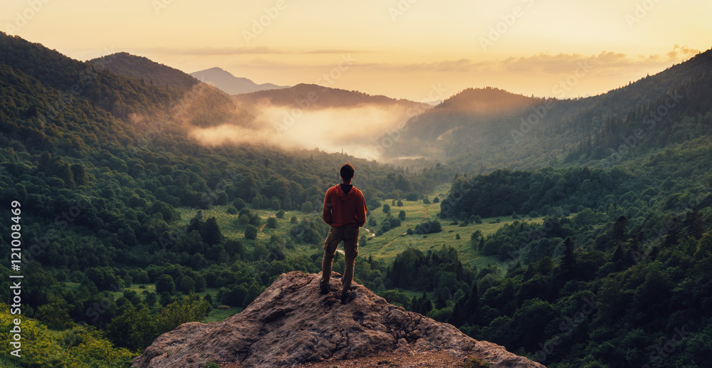 Fototapety, obrazy: Man standing on top of cliff at sunset