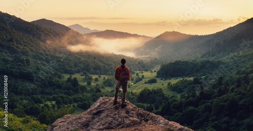 Fotografie, Obraz Man standing on top of cliff at sunset