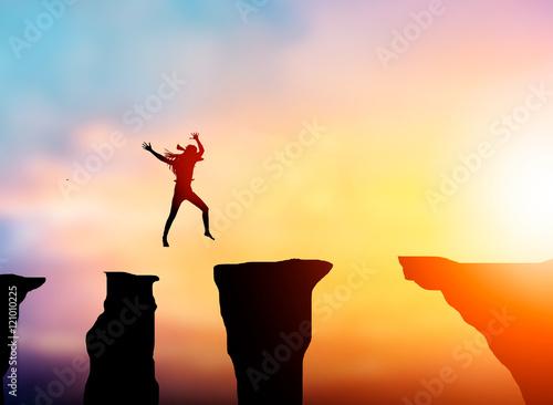 Fotografia  Silhouette businesswoman to jump over obstacles over precipice b