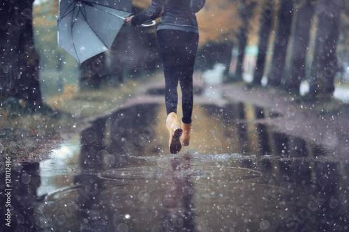 Fotografia autumn landscape city woman umbrella rain puddles of yellow trees