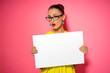 canvas print picture - Your text here. Pretty young excited woman holding empty blank board. Colorful studio portrait with pink background.