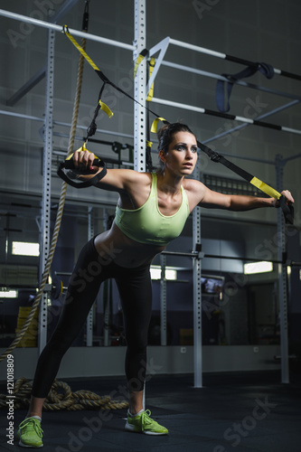 Concept: power, strength, healthy lifestyle, sport. Powerful attractive muscular woman CrossFit trainer working out at the gym