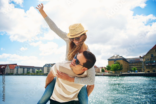 Fényképezés  Fun loving young couple frolicking at a waterfront