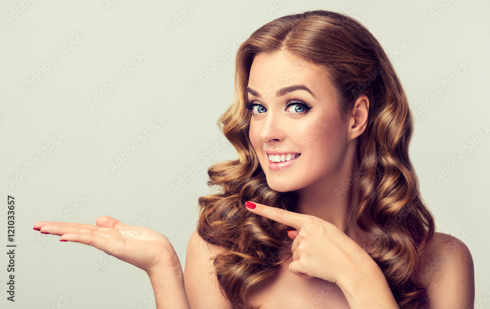 Fototapety, obrazy: Woman surprise showing product .Beautiful girl with curly hair pointing to the side . Presenting your product. Expressive facial expressions
