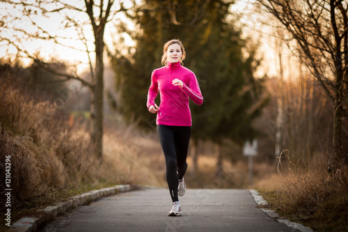 Poster Jogging Young woman running outdoors in a city park on a cold fall/winte