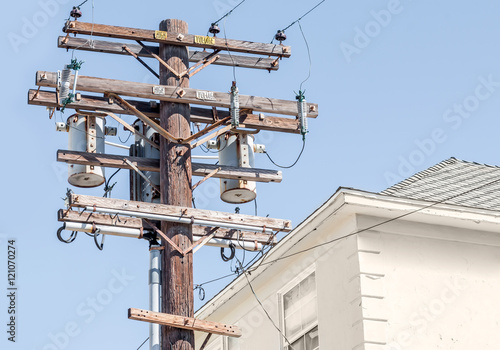 Fotografie, Obraz  Residential wooden power pole with transformers and high voltage lines