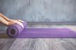 Leinwandbild Motiv Woman rolling her mat after a yoga class