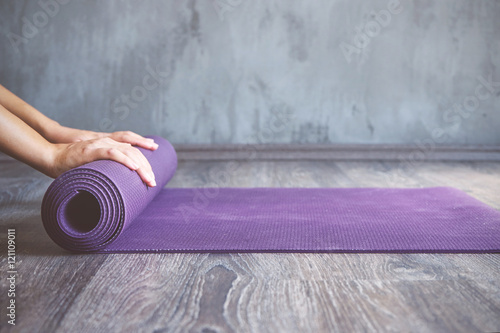 Spoed Foto op Canvas School de yoga Woman rolling her mat after a yoga class