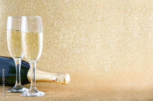 Fotografie, Obraz  Champagne bottle with glass cups on brilliant golden background