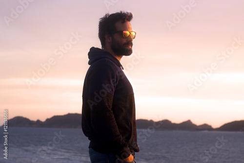 Fotografija  Chico moreno con barba y gafas de sol de espejo mirando al mar, observando su fu