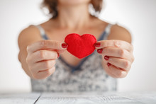 Woman Holding A Heart Symbol In Her Hands