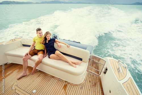 Keuken foto achterwand Schip Romantic vacation and luxury travel. Young loving couple sitting on the sofa on the modern yacht deck. Sailing the sea.
