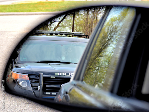 A police car has a motorist stopped for a violation. the drivers view from his side mirror