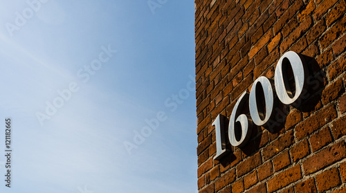 Photo  Building with address sign saying 1600 against blue sky on a sunny day