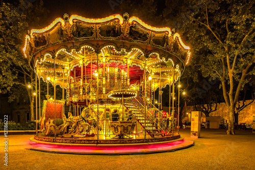 Fotografie, Obraz  Brightly illuminated traditional carousel in Paris France at night