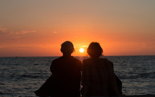 Two Sisters Watching The Final Sunset From A Hawaiian Vacation