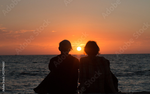 Two sisters watching the final sunset from a hawaiian vacation Fototapet