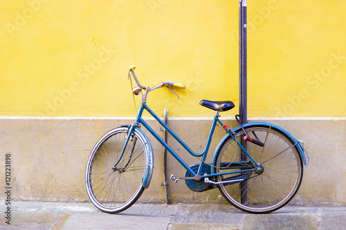 In de dag Fiets Blue old bicycle standing near bright yellow wall.
