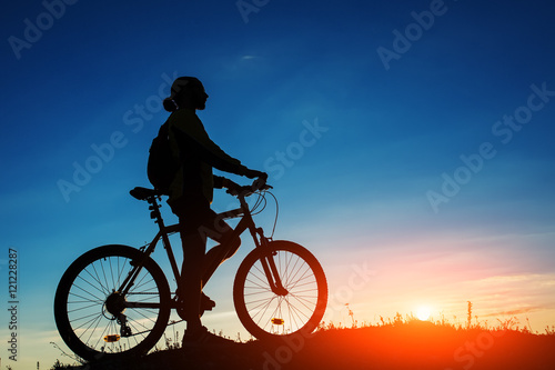 Aluminium Prints Cycling Silhouette of cyclist and a bike on sky background