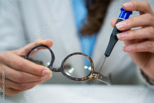Optician repairing spectacles with tool Fototapeta