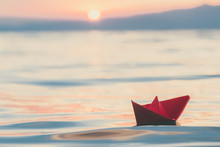 Red Paper Boat Sailing On Water At Sunset. Travel And Vacation Concepts.