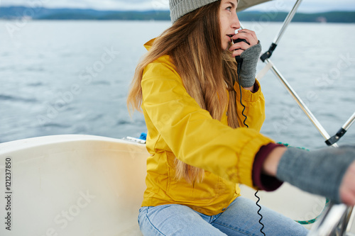 Fotomural  Young woman talking on the radio on the sailboat