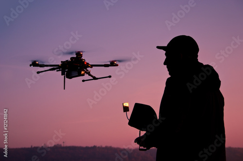 Recess Fitting Military Man operating a drone with remote control. Dark silhouette again