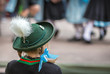 Mädchen mit Trachtenhut blickt auf bayerische Tanzgruppe