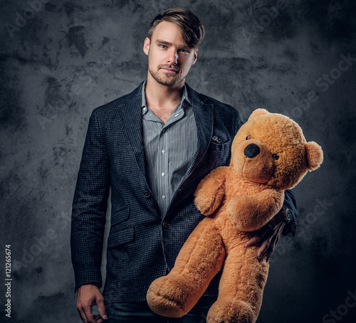Valokuva  Male in a suit holding brown teddy bear.