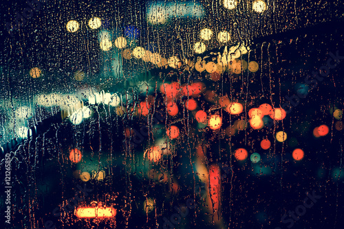 Fotografia City view through a window on a rainy night,Rain drops on window with road light bokeh, City life in night in rainy season abstract background