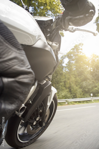 Motorradfahrer fährt auf Straße im Sommer Canvas