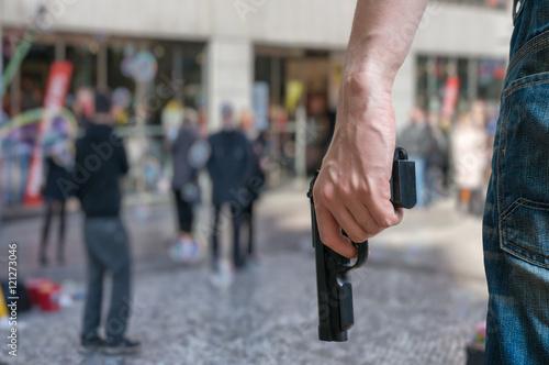 Fotografía  Armed man (attacker) holds pistol in public place