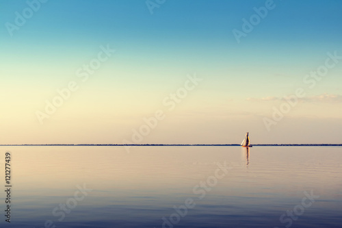 Fotografie, Obraz  Water landscape with white sailing boat on calm waters in the light of the sunset