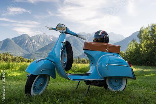 Fotografering  Blaue Vespa vor Bergkulisse auf Feld