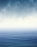 Fog on Blue Ocean. Fog and clouds hovering over the Pacific ocean.  Image displays a pleasing paper grain and texture at 100%.  - 121280681