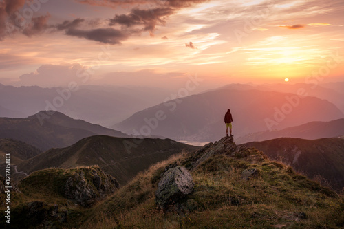 Foto auf AluDibond Schokobraun Man standing on a mountain summit at sunset