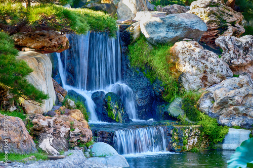 Foto op Canvas Watervallen A small waterfall in a garden