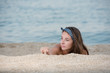 Cute girl with long hair and bow headband lying on the sand