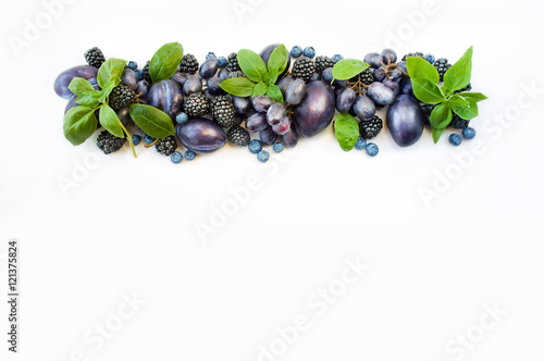 Foto op Canvas Lavendel Group of fresh fruits and berries with basil's on a white background. Ripe blueberries, grapes, plums and blackberries. Top view with copy space.